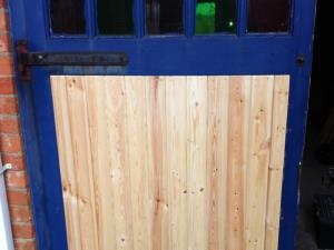 Photo - Repair to rotted panel of a wooden garage door in the Blackburn area, later painted to match